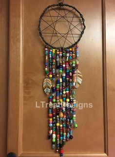 This is my version of a traditional dreamcatcher* I made it with lots of colorful beads, and two hand painted feathers The ring is made from twisted wire It measures 19 1/2 long by 6 1/4 wide *A dreamcatcher is intended to protect the sleeping from negative dreams, while letting happy,