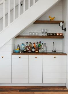 A kitchen faces a staircase fitted with an alcove wet bar boasting stacked salvaged wood floating shelves suspended over white shiplap bar cabinets adorned with square brass knobs topped with wood framing a square stainless steel sink and gooseneck faucet.