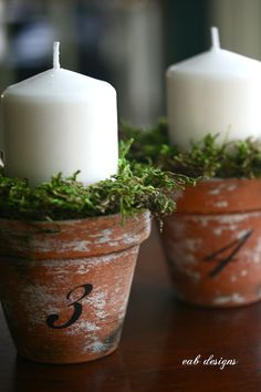 Super easy DIY table decor -- terra cotta pots, white candles and some moss from the craft store.