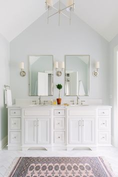 white bathroom, with double vanity, sconces and marble flooring