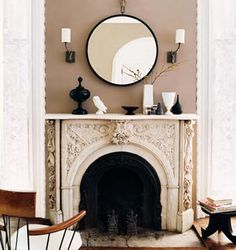 note the contrast between the ornate fireplace and simple round mirror. love the taupe walls too