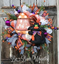 Ba Bam Wreaths  -  Charming & full of vibrant Halloween colors~ this wreath is a feast for the eyes!  Let your door/entry/mantel greet the Halloween season in style! Lots of detail here from the whimsical stripped & checkered designer ribbon, swirly sprays of white, gorgeous florals, stunning purple ornaments, primitive wooden sign and the cutest black cat created by a very talented designer.   (affiliate link)