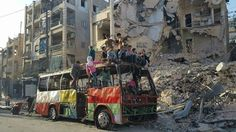 Children play on a burned-out bus in East Aleppo (Credit: BBC)