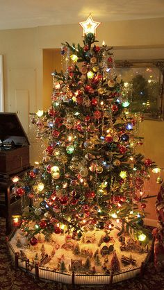 Notice the village at the base of the tree. ~~I do my village throughout the entire kitchen, dining and living areas, i collect Churches, I have the church of the holy sepulcher, which is exquisite, probably my favorite piece in this collection :)