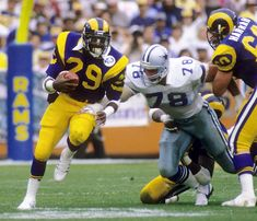 Los Angeles Rams running back Eric Dickerson, who had broken the single-season rookie rushing record in recorded the second season in Dickerson rushed for yards, the current NFL rushing record, and averaged rushing yards per game. Nfl Football Players, American Football Players, Football Helmets, Sport Football, College Football, Nfl Photos, Football Photos, Eric Dickerson, Nfl Rams