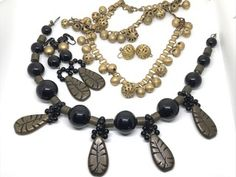 LOT OF VINTAGE COSTUME JEWELRY SETS INCLUDES AN OLD BEADED BAUBLE SET WITH NECKLACE, BRACELET AND EARRINGS AND A CHUNKY BLACK BEADED AND LEAF SET BY ANNE KLEIN WHICH INCLUDES NECKLACE AND EARRINGS.