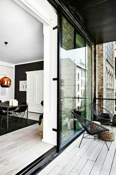 Esszimmer-schwarz-weiße-Gestaltung-Kupfer-Lampe-Balkon-Designer-Stühle-Glastür