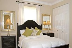 Bed in front of window with curtains- I love the mirrors on the wall with the night stands. Great idea