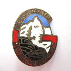 This enamel brooch is from the largest mountain in Germany, the Grossglockner. Its a travel souvenir, dating approximately to the 1950s, which commemorates a trip to this very impressive mountain. It would make an ideal gift idea for your guy, a hiker, or any lover of German or mountain culture. This German hatpin or collectible brooch is primarily gold tone with enamel accents in red, blue and white.