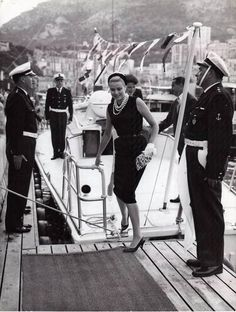 Princess Grace in an LBD form fitting sheath & pearls...(classic) on the deck of an official yacht ..in Monaco.
