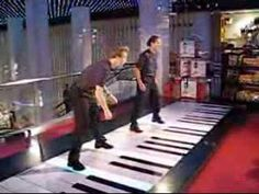 Two guys play Hungarian Rhapsody 2 with their feet on the FAO Schwarz Piano.