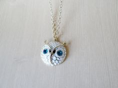 Darling retro-inspired owl features wide aquamarine eyes nestle in a white owl face with gold accents.   Owl charm measures a touch over 1 in diameter.  27 chain slips overhead.