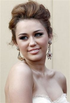 Miley Cyrus at the 2010 Oscar's with upswept hair and smokey eye. Photo Courtesy of AP Photo/Matt Sayles