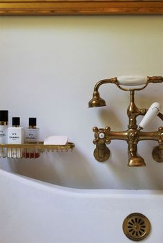 Early century bath and fixtures Cast iron claw foot tub and wall mounted brass taps fittings