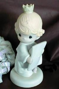 """This darling Precious Moments Figurine is called """"Congratulations Princess"""". Made in 1986 and signed Samuel J. Butcher. This charming porcelain figurine depicts a little girl in her graduation gown and holding her cap with a pink tassel. She wears an adorable little crown in her blond hair.  What a wonderful addition to your collection. Enesco Number 106208. It has the Bow & Arrow mark. Sorry no box.  Item 2989"""