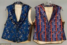 """Two brocade vests, 1830-1850; Both with shawl collars, seven small front buttons, one pair inset front pockets and brown glazed cotton backs: One sapphire blue, brocade of black and ivory floral sprays, blue/black silk buttons, cotton lining, Ch 39"""", L 20""""; One ivory, red and black floral stripes on sapphire blue, blue glass buttons, cotton flannel lining, Ch 42"""", L 21"""""""