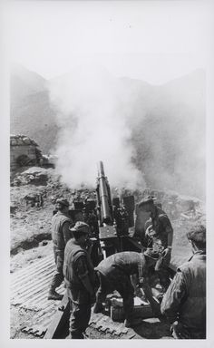 "Marines Fire Artillery Support, 1969 ""On the Way: Leathernecks of the 11th Marines, 1st Marine Division, fire artillery support for Marine infantry units operating in the mountainous terrain west of An Hoa. The battery is one of many positioned atop mountain peak landing zones in support of Operation Taylor Common (official USMC photo by Gunnery Sergeant Chuck Lane)."" From the Jonathan Abel Collection (COLL/3611), Marine Corps Archives & Special Collections. OFFICIAL USMC PHOTOGRAPH"