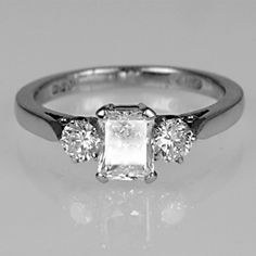 Diamond engagement ring with claw-set emerald cut diamond centre stone and claw-set brilliant-cut diamonds, one either side