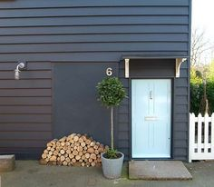 Traditional turned modern with slate gray siding, blue bonnet door, concrete