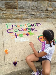 Community art murals with kids in Pittsburgh, pa. Colored sidewalks with chalk and paint . Discussion on beautifying blight neighborhoods Friendship, Strength and Courage theme.