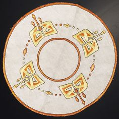 """Arts & Crafts round table mat, The Home Pattern Company for The Ladies' Home Journal, #14001, ca.1908-1918, Celtic motif in orange, yellow and black floss on oatmeal linen fabric, satin, buttonhole, herringbone and outline stitches, 21""""dia., pictured in American Arts & Crafts Textiles (2002)      SOLD $425 March 2003"""