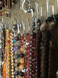 Add curtain hooks  to hang necklaces onto a painted old window screen which hold earrings.