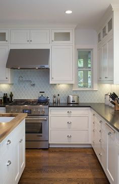 White kitchen using vapor blue glass arabesque backsplash tile. https://www.subwaytileoutlet.com/products/Vapor-Arabesque-Glass-Tile.html#.VWj7ZvlViko