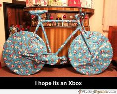 Funny photo of a present wrapped in a gift paper, but is obvious that it is a bike and a caption, I hope its an Xbox
