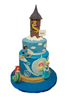 4 Disney princesses make one mighty movie themed cake.  Cinderella, Ariel, Jasmine, Rapunzel.