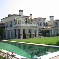 A combination of French country estate and California classic chic meet in this beautiful house with tiles roof, tall windows with blue shutters, rooftop garden patio, and sunny pool. Design and photo by Giannetti Architects