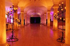 Old Royal Naval College London - Spiral floor standing candelabra with battery-powered candles, uplighting in amber and magenta and black backdrop by www.stressfreehire.com #venuetransformers