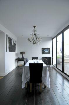 Spisestuen har fått et svartmalt plankegulv, som står i fin kontrast til de hvite veggene. Brede vindusflater i spisestuen slipper masse dagslys inn, og gir en følelse av å sitte på terrassen.