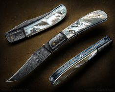 © Don Hanson Custom Folders: Hanson Damascus Pearl Madness Folder Knife Specifications: Blade: 3-3/8 inches Hanson Damascus. Closed Length: 4 inches. Details: Bolsters are Hanson Damascus. Scales: Premium White Mother of Pearl. Anodized Titanium liners. Solid gold thumb stud.