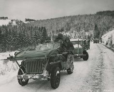 Bullet holes in the windshield of this Jeep are a testament to the faithful service of the Medics of the 84th Division as they evacuate wounded soldiers in their makeshift Jeep ambulance. The Medics are carrying two soldiers wrapped up in blankets to keep them warm in the frigid cold. The litters are strapped to a makeshift frame attached to the flat-hooded Jeep 4x4. This Jeep caravan was part of the 1st Battalion, 334th Infantry Regiment. Image was taken on January 9th, 1945 ~