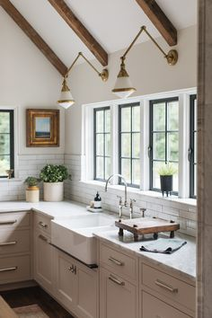 Kitchen wall sconce, reclaimed wood beams, vaulted ceiling, dark window panes, antique art, silver faucet, polished nickel, marble, flush inset cabinets, white cabinets, off white cabinets, apron front sink, subway tile,
