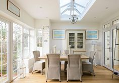 The inside view of an Edwardain style orangery functioning as a dining area, with Aluminium French Doors in White