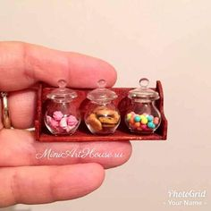 Miniature sweets in the glass jars on the wood shelf.