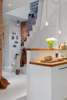 białe schody w otwartym widoku korytarza z kuchnią,biała kuchnia otwata na korytarz z białymi schodami i ścianą z czerwonej cegły,otwarrta p...