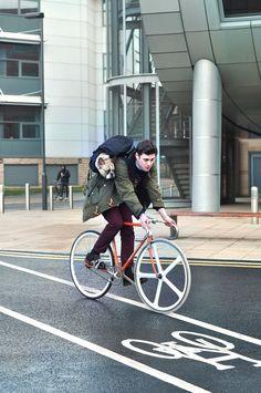 A dog riding a man riding a bike