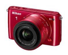 """Digitalni fotoaparat 1 S1 Nikon Kada dođe do odlučnog trenutka, morate da budete spremni. Međutim, šta ako vaš """"nosi se svuda"""" fotoaparat nije dorastao tom zadatku? Sistemski fotoaparat sa zamenljivim objektivima Nikon 1 S1 je uvek spreman za akciju. Prikladan je i lako se koristi koliko i kompaktan fotoaparat, ali je mnogo brži i znatno moćniji, sa boljim kvalitetom slike."""