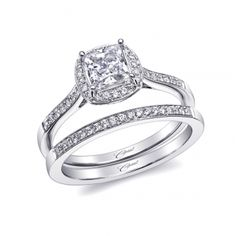 This elegant engagement ring is made for a 5mm princess cut diamond. Fine pave set diamonds decorate the cushion shaped halo and shoulders of the ring. Milgrain edging adds the finishing touch. Shown with matching pave diamond band.