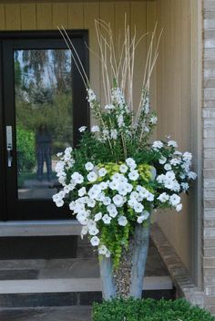 White, green and zinc looking pot = welcoming. Love the idea of using branches in the center of the pot. Adds height, and makes for a ready trellis for the vines.