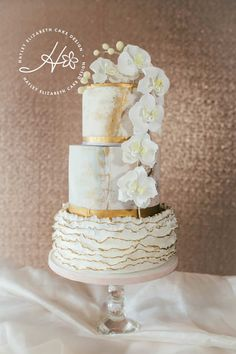 Luxury wedding cake with gold foil marble effect icing sugar flower orchids and ruffles. Elegant wedding cake luxury cake design wedding cake inspiration beautiful wedding cakes three tier wedding cake white and gold wedding cake. White And Gold Wedding Cake, Sweet Table Wedding, Wedding Cake Rustic, Elegant Wedding Cakes, Elegant Cakes, Beautiful Wedding Cakes, Wedding Cake Designs, Trendy Wedding, Luxury Wedding Cake Design