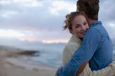Portrait of smiling woman hugging man on beach