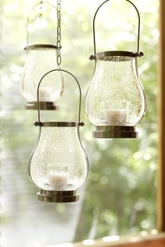 Glass lanterns lend glowing warmth to your outdoor space. Hang them at different heights for added visual interest.