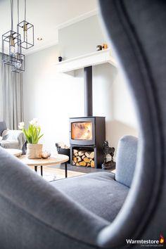Warmtestore uw haardenspecialist | Vrijstaande houtkachel met natuurstenen vloerplaat die op gelijke hoogte is gebracht als de echte houtenvloer in de woonkamer.