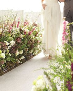 Create an enchanting ceremony path by adding untamed posies to a wooden flower frame. Echo the look with an equally abundant bouquet. At the reception, recycle your makeshift garden into an escort-card display.  Thanks to a pair of ingenious wooden panels, you can walk toward your groom flanked by hundreds of wildflowers, such as larkspur, lisianthus, bridal wreath spirea, and lepidium, pictured here.