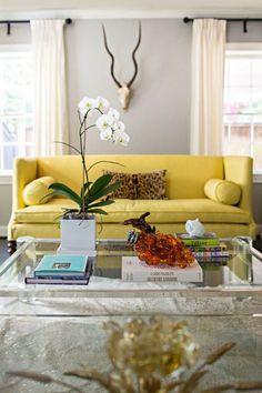 sofá amarelo na decoração da sala de estar. mesa de centro de vidro com vaso de flores brancas