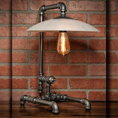 A handmade industrial chic table lamp that is sure to add a truly charming accent to any home or office. With its unique and re-imagined blend of metal pipe fittings and mid-century frosted glass shade create a unique lamp that will surely add a warm and welcome atmosphere. This is sure to become the topic of conversation among guests, friends, family or clients.  All TMG-DZN lamps will accept all Incandescent, CFL or LED medium base bulbs. Light socket rated for up to 75 watt bulb.  Bulbs…