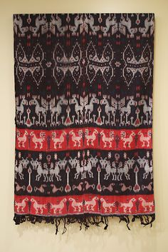 Hinggi cloth of warp ikat with cotton warp and weft, Indonesian, 20th century, KSUM 1983.1.952  This hinggi, which is a garment that men would wrap around their lower body is symmetrical both horizontally and vertically. The warp is doubled when it is tied for dyeing, so the images appear reflected across the mid-section.